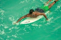 Le surfer nage à bord Image stock
