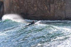 Le surfer prend une vague, sur une planche de surf, des glissi?res le long de la vague, ? l'arri?re-plan de la montagne, Sorrente photo stock