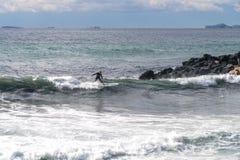 Le surfer prend une vague, sur une planche de surf, des glissi?res le long de la vague, ? l'arri?re-plan de la montagne, Sorrente image stock