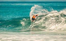Le surfer s'étend à bord sur la vague Photographie stock libre de droits
