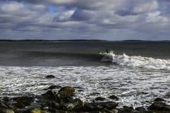 Le surfer surfe une vague parfaite un jour ensoleillé Image libre de droits