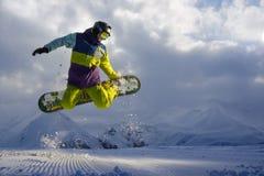 Le surfeur fait le tour sautant la neige disperse des morceaux Photographie stock