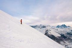 Le surfeur se tient sur la colline de neige Photos libres de droits