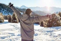 Le surfeur tient le dessus de montagne avec ses bras augmentés Images libres de droits