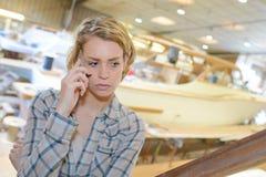 Le surveillant féminin avec surprise regarde le worke d'entrepôt Image libre de droits