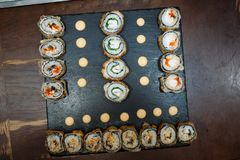 Le sushi roule l'ensemble sur le conseil noir sur la table en bois images libres de droits