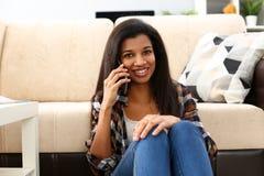 Le svart kvinnah?llen i handmobiltelefon hemma royaltyfria bilder