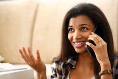 Le svart kvinnah?llen i handmobiltelefon hemma royaltyfri foto