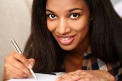 Le svarta kvinnan skriv berättelsen i anteckningsbok arkivbild
