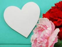 Le symbole blanc de forme de coeur et l'oeillet artificiel fleurissent le jour de valentines Photos stock