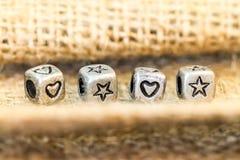 Le symbole d'étoile et de coeur cubent des perles sur le sockcloth Image stock