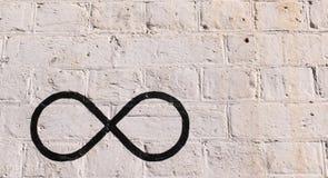 Le symbole d'infini dessiné dans le noir sur un mur de briques Photo libre de droits