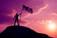 Le symbole d'un homme avec le drapeau des Etats-Unis se tient sur le dessus de la montagne photographie stock