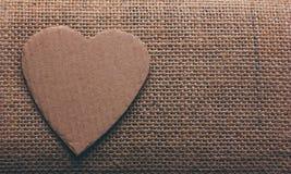 Le symbole de coeur a coupé du carton sur le plan rapproché de toile de jute Images libres de droits