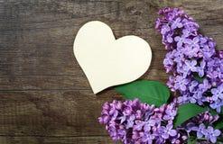 Le symbole de coeur de l'amour et du lilas fleurit sur un fond en bois photo stock