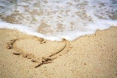 Le symbole de coeur sur le sable et la mer ondulent Image stock