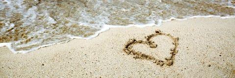 Le symbole de coeur sur le sable et la mer ondulent Images stock