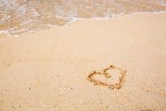 Le symbole de coeur sur le sable et la mer ondulent Photos libres de droits