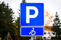 Le symbole de fauteuil roulant dans un parking marque le parking handicapé Photos stock