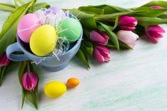 Le symbole de vacances de Pâques a peint des oeufs dans la tasse bleue et les tulipes roses b Images libres de droits