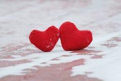 Le symbole des coeurs tricotés chauds rouges de l'amour deux se trouvent ensemble sur a Images stock