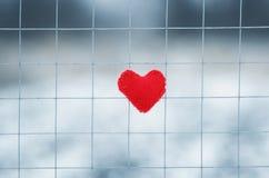 Le symbole du rouge d'amour a tricoté le coeur se trouvant sur des barres en métal du marais Photos stock