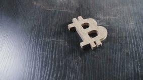 Le symbole en bois de bitcoin se trouve sur une table poussiéreuse banque de vidéos