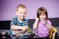Le syskongruppen med vattenfärger som färgar påskägg royaltyfria foton