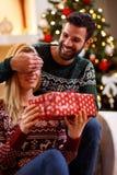 Le täckande kvinna` s för mannen synar med händer och att ge gåvaasken royaltyfri fotografi