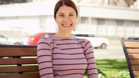 Le tätt upp ståenden av den unga kvinnan för härlig brunett som ler i staden Sommardag utanför lager videofilmer