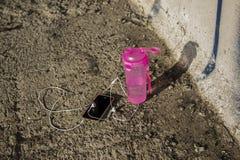 Le téléphone avec de l'eau les écouteurs et pour la sportive Image libre de droits