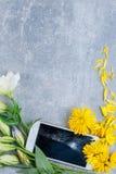 Le téléphone cassé se situe en fleurs ci-dessous sur un fond en pierre image libre de droits