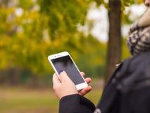 Le téléphone dans les mains d'une jeune fille Photographie stock