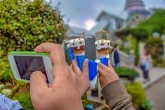 Le téléphone de main de participation de main de femme prennent une photo photos stock