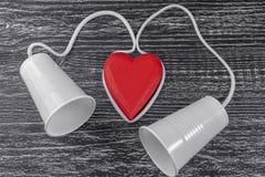 Le téléphone est fait de tasses en plastique blanches et une corde blanche est étendue autour d'un coeur en bois rouge photos libres de droits