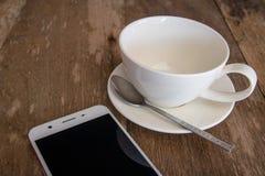 Le téléphone est placé près d'une tasse de café blanc sur un vieux bois tab1 Photos stock