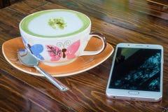 Le téléphone est placé près de la tasse de café Photographie stock libre de droits