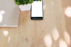 Le téléphone et le journal intime futés réservent sur le fond en bois de table avec l'espace de copie Photos stock