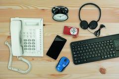 Le téléphone et le smartphone blanc de ligne terrestre de bureau, l'ordinateur de clavier et l'horloge de table ont utilisé les i photo libre de droits