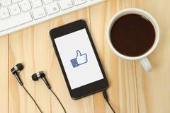 Le téléphone intelligent avec Facebook manie maladroitement vers le haut du signe Images stock