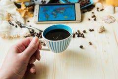 Le téléphone intelligent de presse de main avec la tasse de café et l'écouteur, concept tout peut faire sur votre main par le tél Photographie stock libre de droits