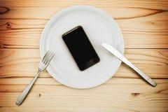 Le téléphone intelligent mobile a servi de dîner du plat blanc photo stock
