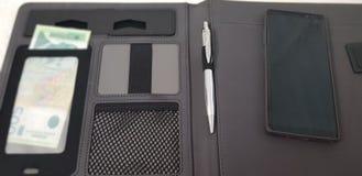 Le téléphone intelligent s'étendent sur le dossier en cuir ouvert avec un stylo et une monnaie fiduciaire serbe photo libre de droits