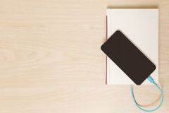 Le téléphone intelligent s'est relié au vieux livre à un câble Photographie stock libre de droits