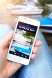 Le téléphone portable avec des bateaux pour l'offre de loyer holded à la main Images libres de droits