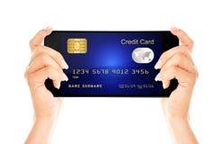Le téléphone portable avec la carte de crédit holded à la main d'isolement au-dessus du petit morceau Photographie stock libre de droits