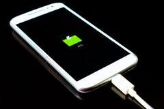 le téléphone portable charge sur un fond noir images stock