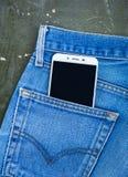 Le téléphone portable dans des jeans empochent sur le vieux fond en bois Vue supérieure Photos stock