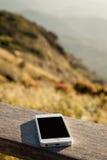 Le téléphone portable a mis dessus le bois à la crête de la montagne Image stock