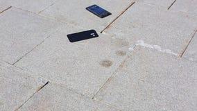 Le téléphone portable tombe sur la terre et les fentes dans des pièces, la main de l'homme l'enlevant Le téléphone sensoriel tomb banque de vidéos